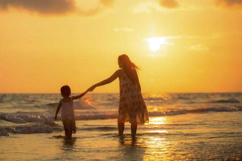 Масть с ребенком встречают закат на пляже
