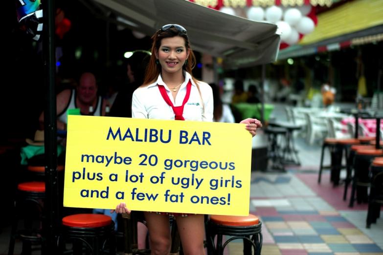 Девушка с рекламой у гоу-гоу бара на улице Бангла