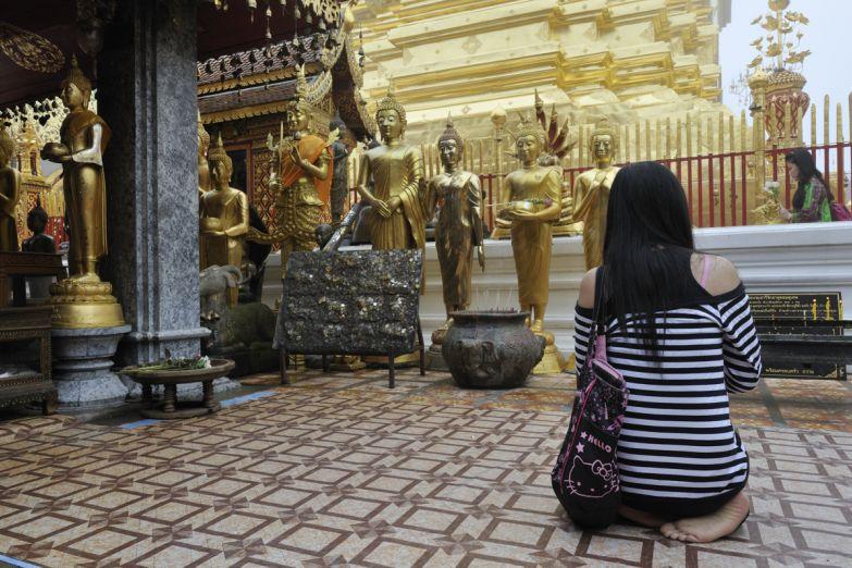 Девушка молится в храме Изумрудного Будды